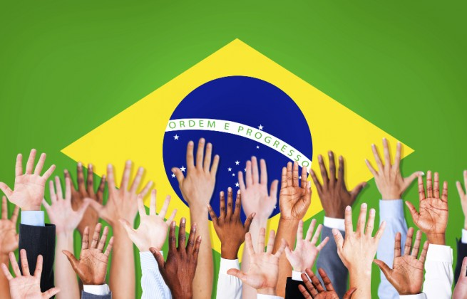 Group of Multi-Ethnic Arms Raised and a Flag of Brazil as a Background votacao brasil bandeira voto participacao